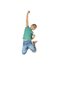 Mixed race child wearing ear buds, jumping and holding his arm out with fist, isolated on white background